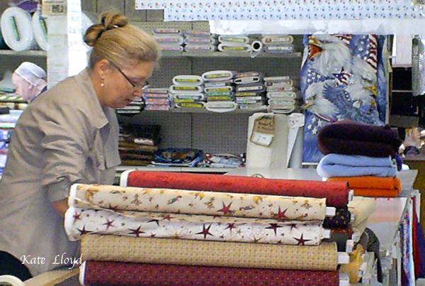 An English employee cutting fabric at Zook's Fabrics.